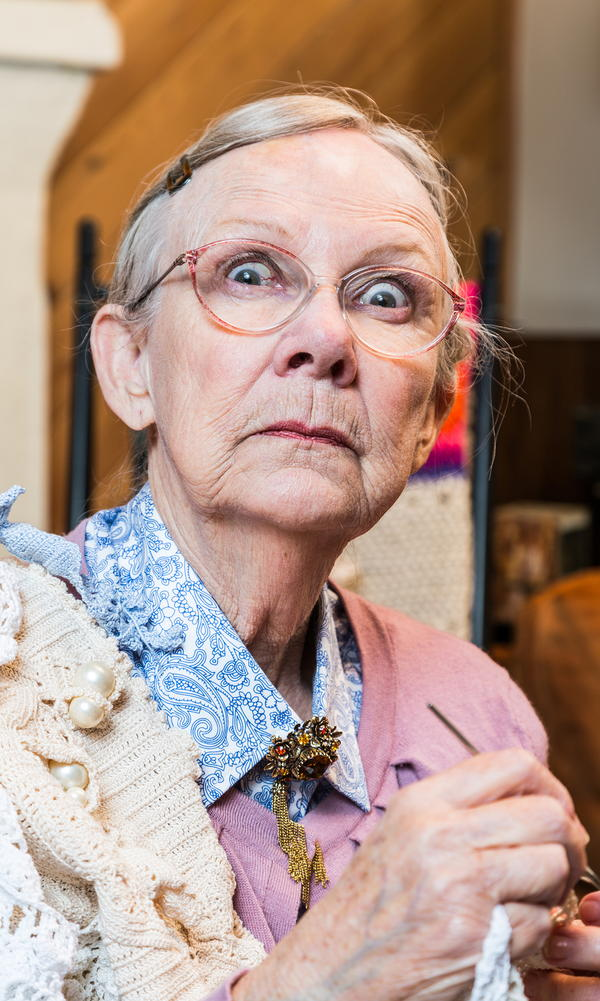 Woman crocheting while glaring at camera