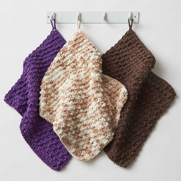Image shows three dishcloths hanging on a bar in purple, beige variegation, and brown. These are the Super Speedy Textured Dishcloth pattern.