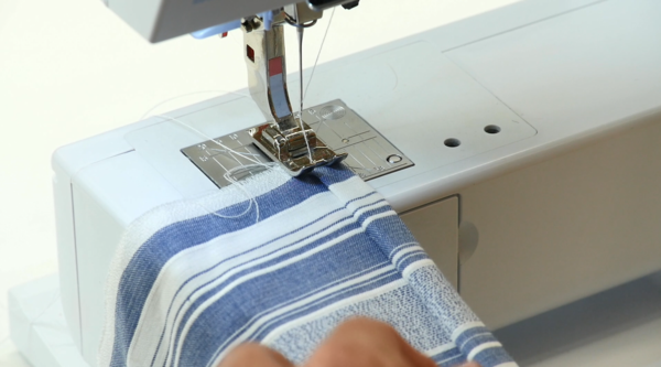 Image shows sewing the DIY kitchen boa fabric with a sewing machine.