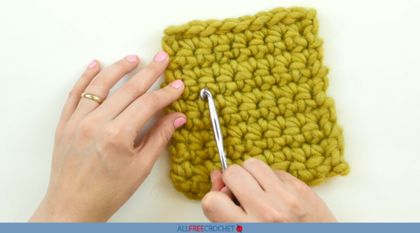Image shows a swatch of yellow yarn and hands with one holding a crochet hook to show counting stitches.