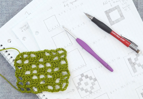 Image shows a gray carpet background with notebook and piece of loose paper with filet crochet designs and notes. On top of the paper is a small green filet crochet swatch, a crochet hook, and mechanical pencil.