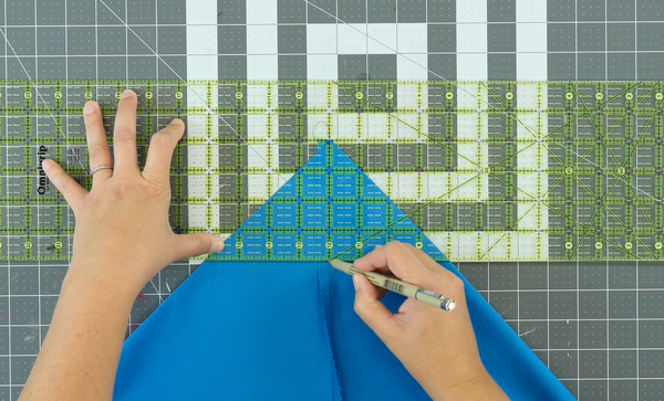 Image shows a cutting mat in the background. The sewn blue bag piece is being measured by a quilting ruler and a person is marking the measurement needed with a fabric marker.