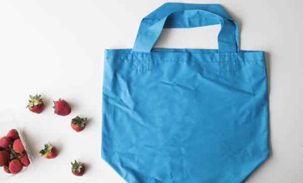 Image shows the finished bag on a white background. There are strawberries to the left of the bag.