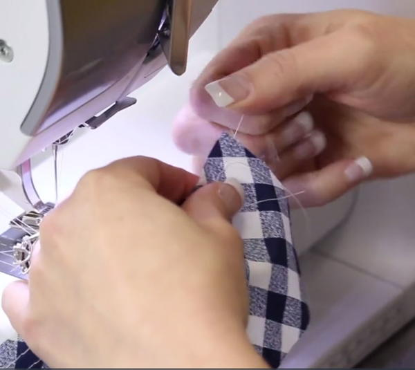 Image shows a person pulling thread after the fabric was sewn on a sewing machine.