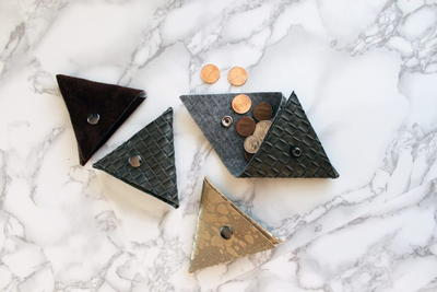 Image shows a gray and white marbled background and four No-Sew Triangle Coin Purses. One is open and coins are spilling out.
