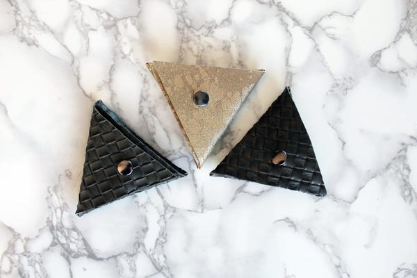 Image shows three of the no-sew triangle coin purses on a light marbled background.