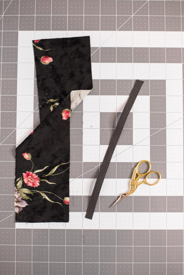 Image shows a piece of fabric, length of elastic, and scissors sitting atop a cutting mat.