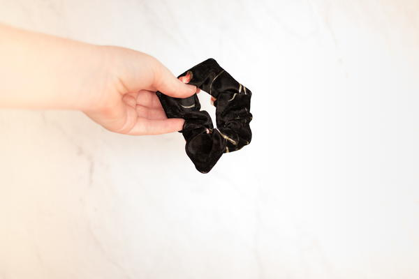 Image shows a hand holding up a black scrunchie.