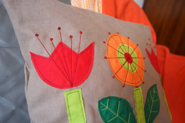 Image shows a close up of the flowers on the finished cushion sitting on a chair with a red blanket draped over the back and seat.