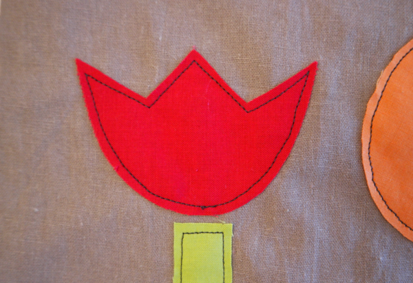 Image shows close-up of a red embroidered flower on the cushion. How to Applique Flowers to the Cushion - Step 1