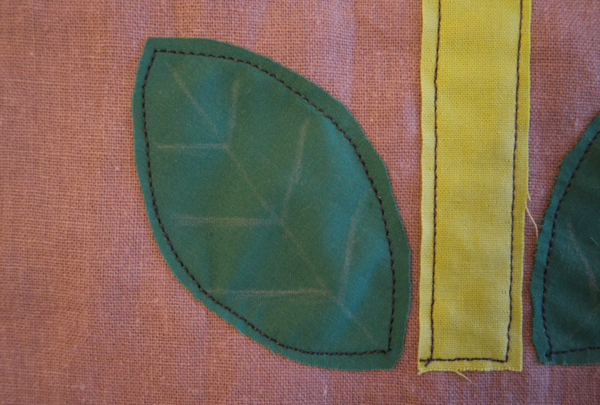 Image shows close-up of one embroidered leaf on the cushion. How to Embroider the Flowers - Step 1