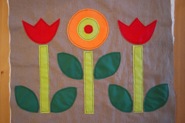 Image shows close-up of three embroidered flowers with dark green leaves on the cushion. How to Applique Flowers to the Cushion - Step 4