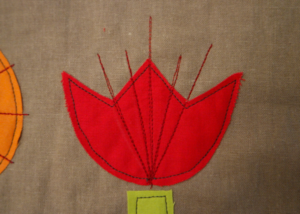 Image shows close-up of a red embroidered flower with four vertical lines added, on the cushion. How to Embroider the Flowers - Step 2