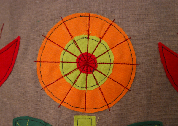 Image shows close-up of an orange embroidered flower with 12 lines added through the center, on the cushion. How to Embroider the Flowers - Step 3