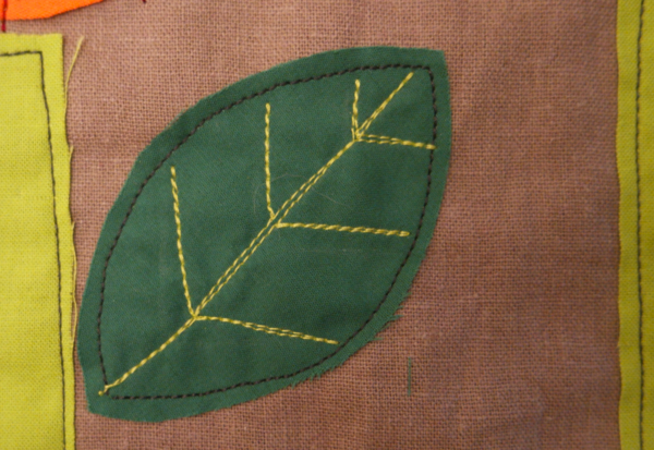 Image shows close-up of a dark green embroidered leaf with vein accent lines, on the cushion. How to Embroider the Flowers - Step 4