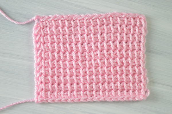 Image shows a rectangle swatch in pink showing the Tunisian crochet simple stitch.