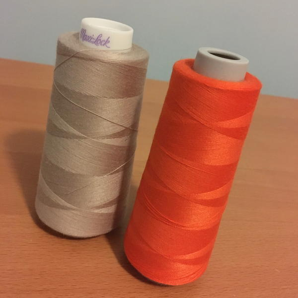 Image shows two spools of thread used for sergers set upright on a wood surface.