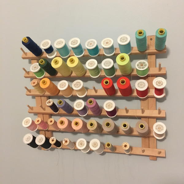 Image shows a thread holder on a wall with various spools of thread attached.