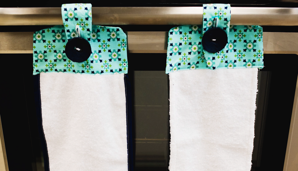Image shows two finished towels hanging side-by-side on the handle of a stove.