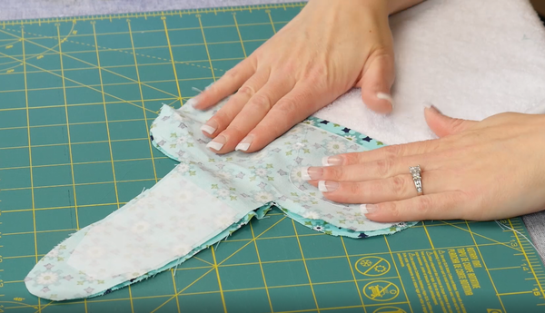 Image shows fabric pattern pieces being put right sides together over the terry cloth towel.