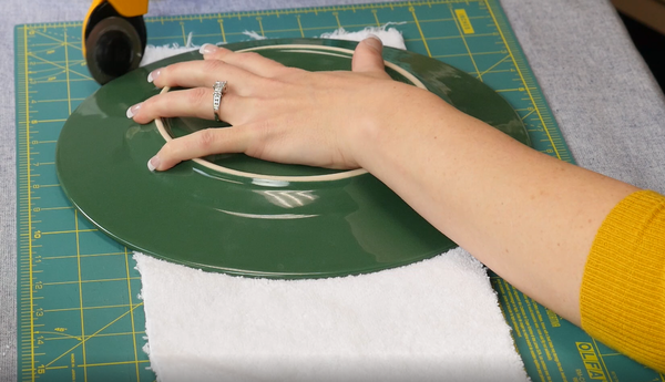 Image shows a plate being used to trim curved edges on the bottom of the terry cloth towel.