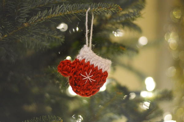 Image shows the Tunisian Mitten Ornament hanging on an evergreen tree.