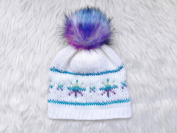 Image shows the I Wish It Would Snowflake Hat sitting on a light gray fur background.