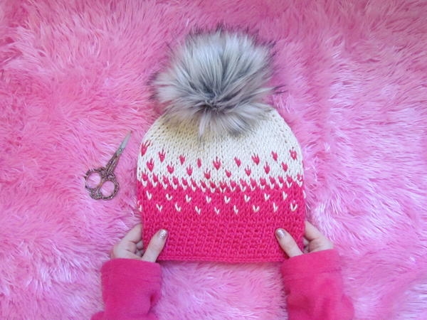 Image shows the Faded Tunisian Beanie sitting on a pink fur background with hands holding the bottom. There are scissors set at the left of the hat.