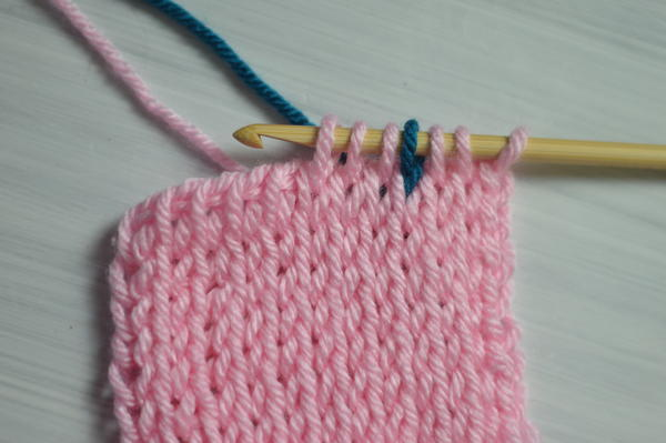 Image shows the first step for carrying colors in Tunisian crochet.