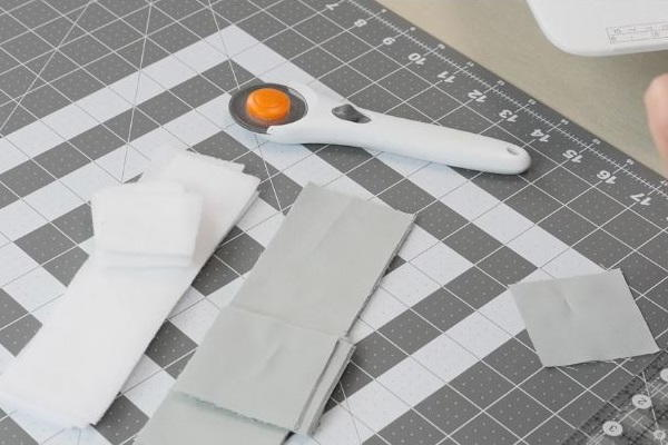Image shows a cutting board with strips of fabric and a rotary cutter sitting on top.