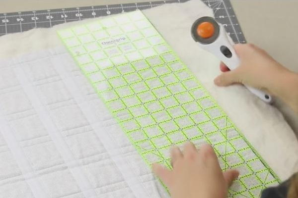 Image shows the piece of light fabric with all of the Velcro pieces attached sitting on a cutting mat. A ruler is sitting above and a hand is holding a rotary cutter in preparation of cutting the fabric.