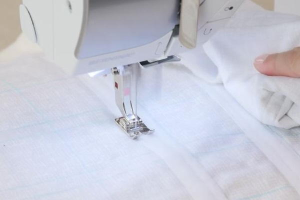 Image shows the another stitch to secure the Velcro being sewn with a machine to the piece of light fabric.