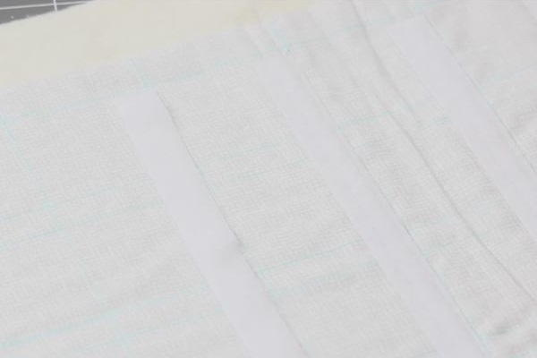 Image shows a piece of light fabric with blue lines and pieces of Velcro aligned to fit the lines.