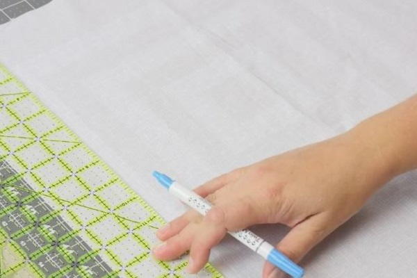 Image shows a piece of light fabric being measured with a quilt ruler. A hand is holding a fabric marking pen.