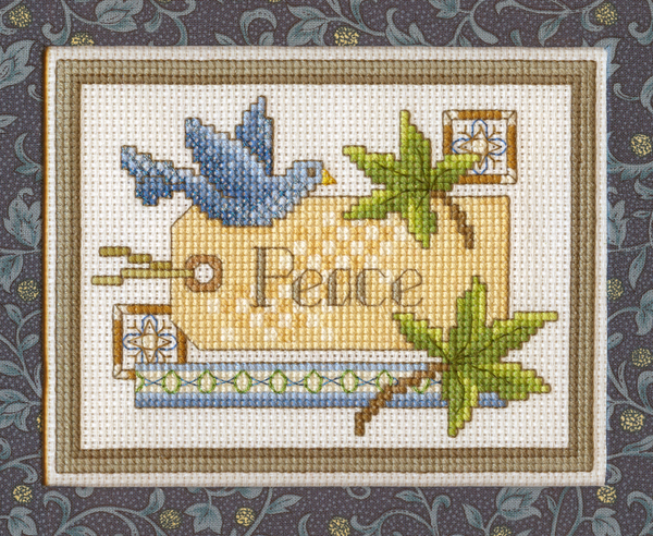 "Image shows a Beautiful Peace Label cross-stitch design. There is a stitched gift tag that has ""Peace"" written on it. There are leaves and a blue bird."