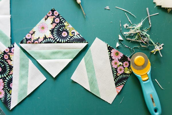 Image shows three quilt blocks and a rotary cutter.