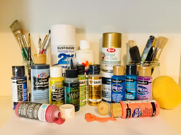 A variety of different craft paints, as well as brushes and tools