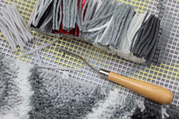 Image shows preparation to rug latch hook: canvas, cut yarns, latch-hook.