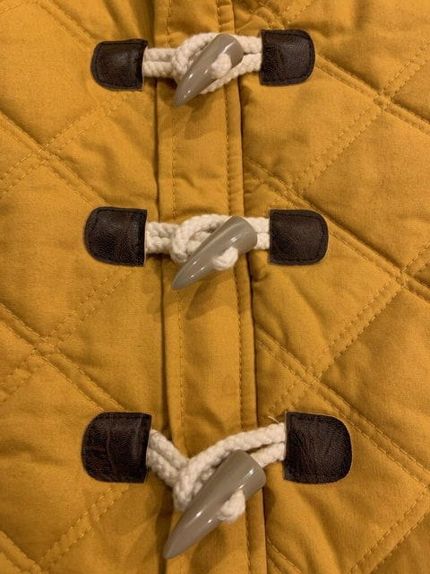 Images shows a close-up of a coat with three toggle closures.