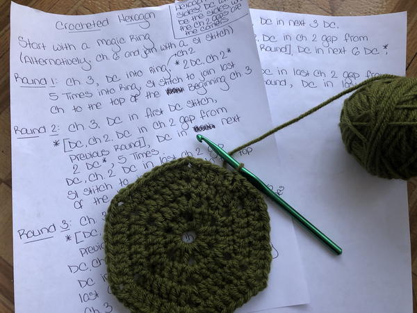 Image shows two pieces of printer paper with a crochet pattern written down. Lying on the paper is a dark green crochet hexagon in progress with a crochet hook and a ball of yarn attached.