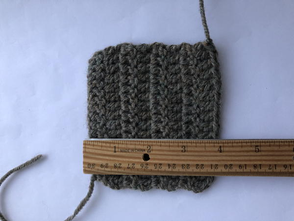 Image shows a crochet swatch on a light background. There is a wooden ruler measuring horizontally across.