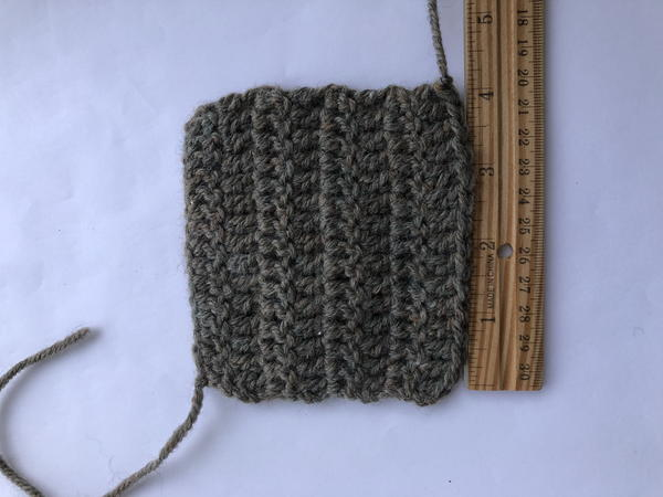 Image shows a crochet swatch on a light background. There is a wooden ruler measuring the right side.