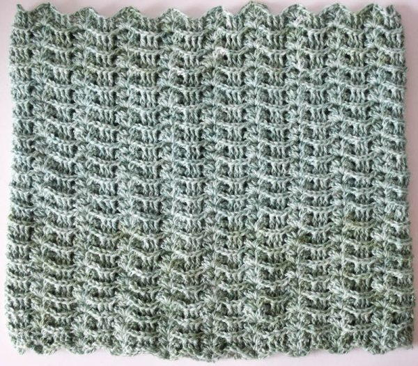 Image shows a textured wave crochet stitch swatch in a muted blueish-green. It is on a light gray background.