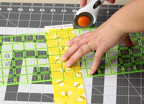 Image shows a close up of a gray cutting mat on a beige table. A hand is using the rotary cutter to cut the fabric at the edge of the ruler on the mat.