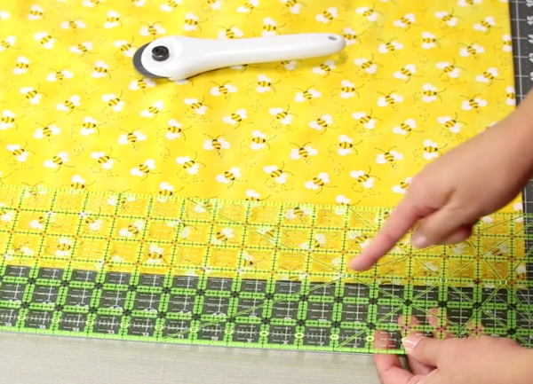 Image shows a close up of a gray cutting mat on a beige table. A hand is adjusting the quilting ruler over the yellow fabric on the mat. Another hand is pointing to a measurement on the ruler. The rotary cutter is sitting on the fabric.