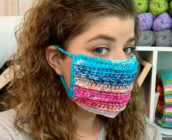 Image shows a woman wearing a colorful crochet mask.