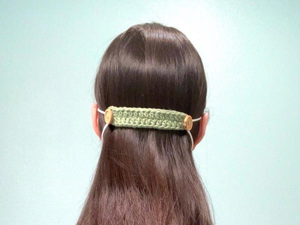 Image shows the back of a woman's head with a light green crochet ear saver holding elastic loops of a mask.