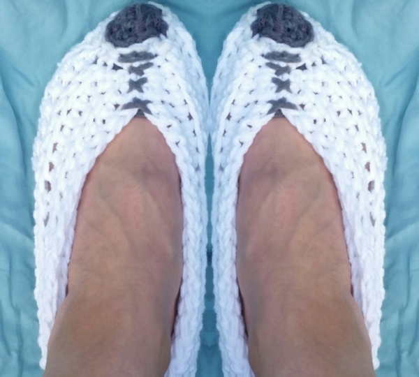 Image shows one pair of the quick crochet slippers being worn.