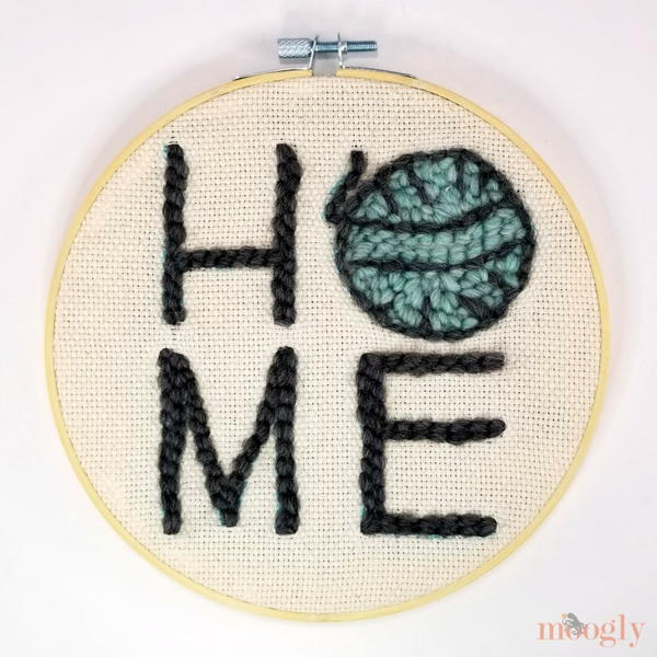 "Image shows a punch needle embroidery design spelling out ""HOME"" with yarn as the ""O"". It is inside a unfinished wood embroidery hoop."