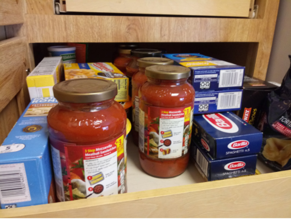 A pantry stocked with dried pasta and pasta sauce